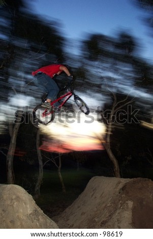 freestyle BMX rider does dirt jump with sunset as background - stock photo