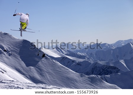 Freestyle ski jumper with crossed skis in snowy mountains