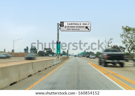 Freeway carpool lane entrance with overhead sign.Yellow and white lines.Blurred motion.Two way traffic with concrete barrier.Blue sky background.Nice commuter, traveling concept.Horizontal scene. - stock photo