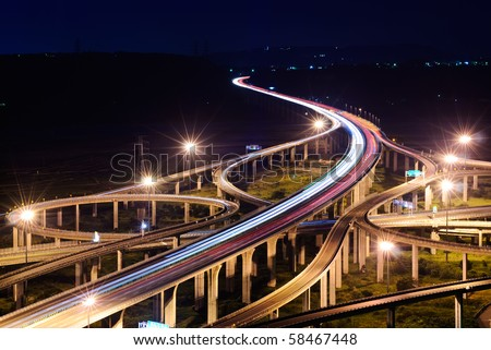 Freeway in night with cars light in modern city. - stock photo