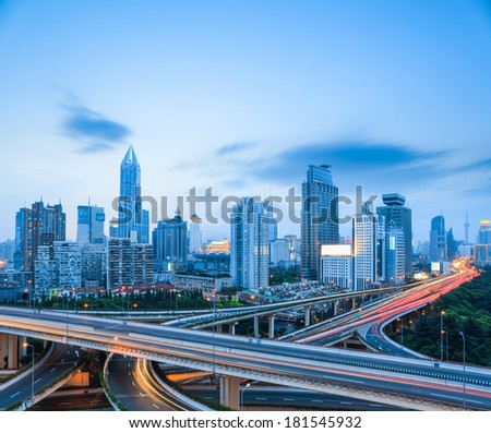 freeway interchange with modern city skyline in shanghai , road transportation infrastructure.  - stock photo