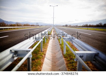 Freeway on a sunny day trough scenic green meadows.Motorway traveling long distance.Asphalt highways road in rural scene use land transport and traveling concept.Vehicular traffic.No traffic - stock photo