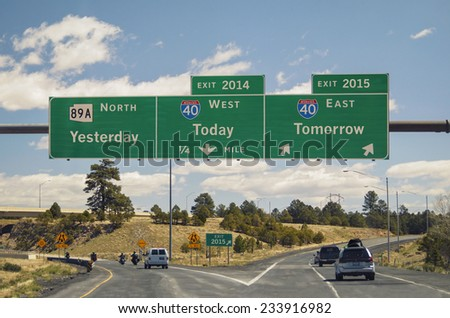 Freeway sign on western US highway New Year's concept yesterday today and tomorrow as destinations with exits for old year 2014 and new year 2015. Copy space use News MT Gothic Bold to match text - stock photo