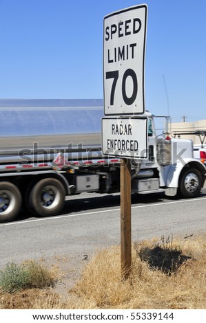 Freeway speed limit sign with motion blurred semi truck in background - stock photo