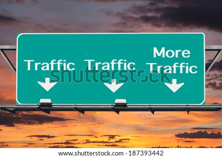 Freeway to more traffic road sign with sunset sky. - stock photo
