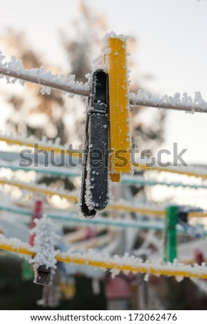 Freeze dried- frozen pegs hang from a rotary washing line on a cold icy winters day. - stock photo