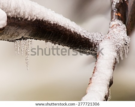 Freeze inter view to icicles on twigs and icy boulders above rapid stream. Reflections of head lamp in icicles. - stock photo