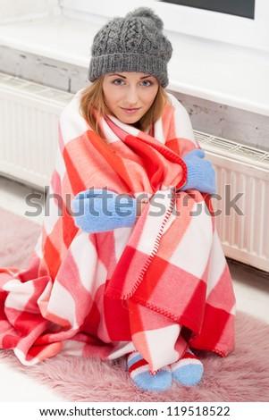 Freezing girl neat the heater - stock photo