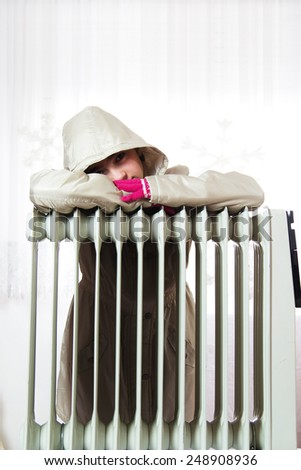 Freezing Young Girl in Winter Jacket Near a Heater. - stock photo