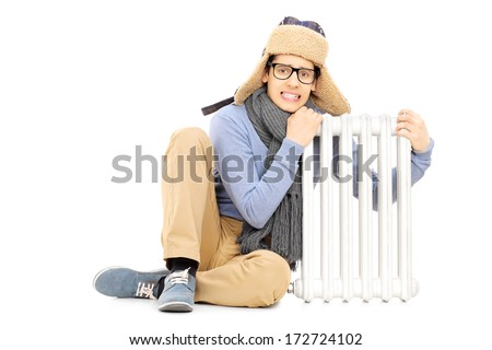 Freezing young guy in winter hat and scarf sitting next to radiator isolated on white background - stock photo