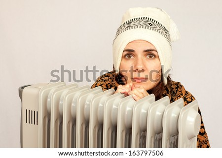 Freezing young woman near a heater - stock photo