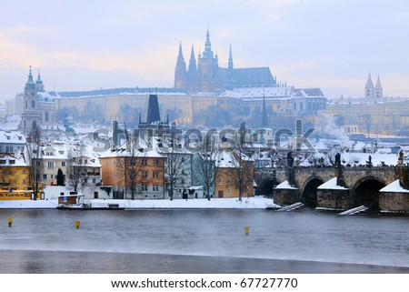 Freezy foggy evening snowy Prague with gothic Castle and Charles Bridge
