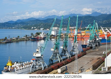 Freight cargo ships, railway wagons and cranes in seaport - stock photo