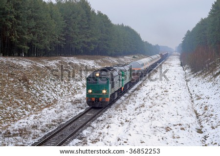Freight diesel train passing the snowy forest