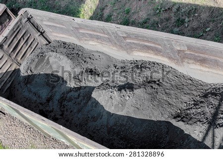 Freight railroad cars with a black fine coal moved by rail. Top view. Small motion blur. - stock photo
