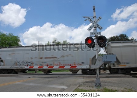 Freight train at crossing gate - stock photo