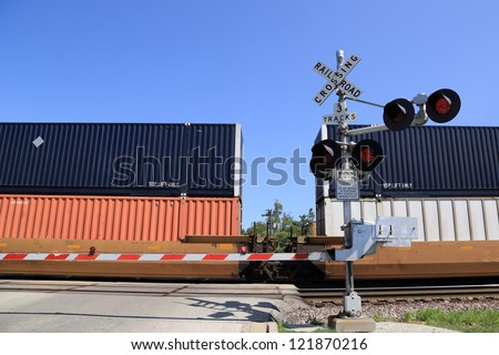 Freight train at railroad crossing gate - stock photo