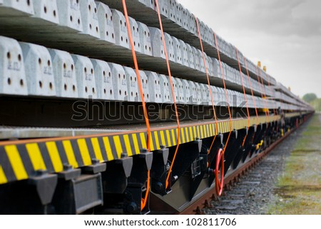 Freight train cargo wagons loaded with concrete sleepers and shallow DOF - stock photo