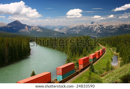 Freight train moving along Bow river in Canadian Rockies, Banff National Park, Alberta, Canada - stock photo