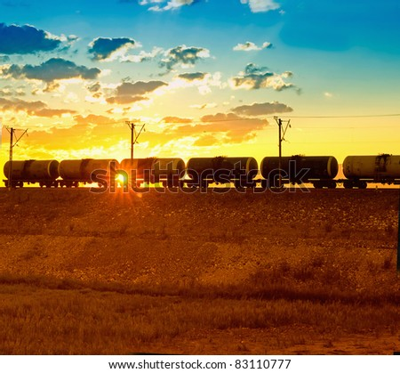 Freight train passing by on sunset beam - stock photo