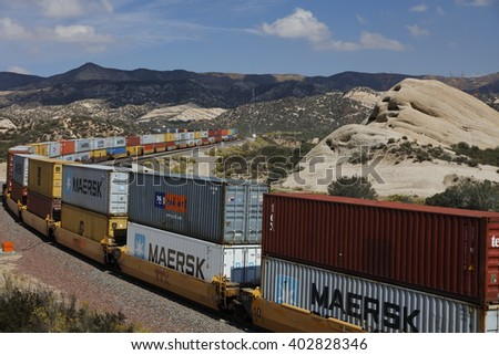 Freight train with cargo containers winds its way through mountain landscape, California