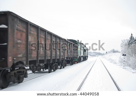 Freight train with coal (or gravel). After a plentiful snowfall. (Partly small motion blur) - stock photo
