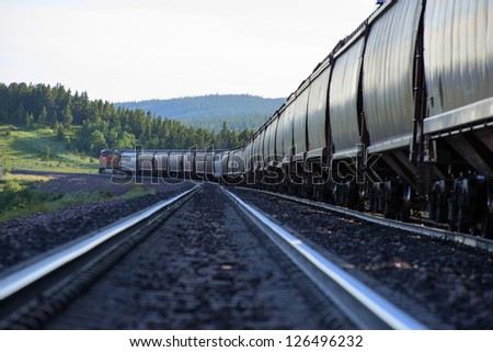 Freight train with hopper cars beneath mountains - stock photo