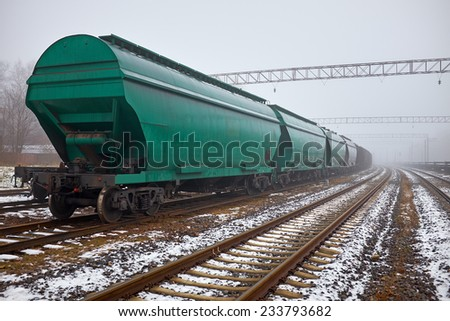 Freight train with hopper cars in the fog - stock photo