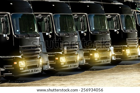Freight trucks with lights on parked on parking, image in solarisation technique - stock photo