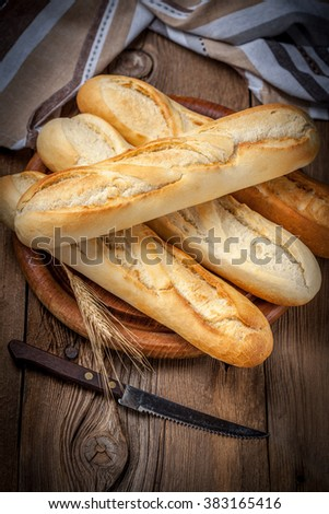 French baguettes on old wooden table. Selective focus. - stock photo