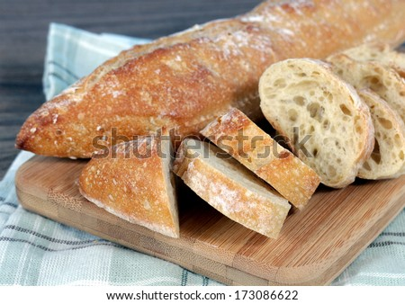 french bread baguette on cutting board with its slices - stock photo
