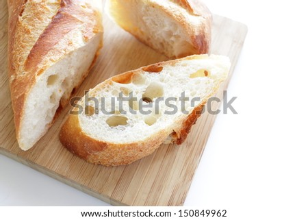 french bread, sliced baguette on wooden cutting board - stock photo