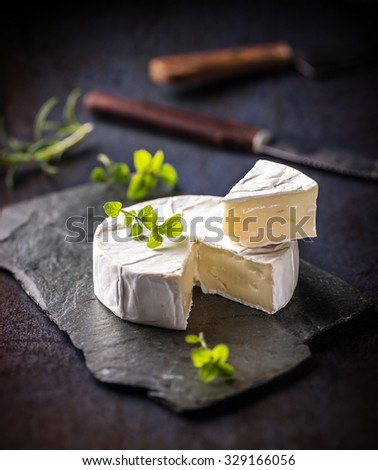 French camembert pieces served on slate surface - stock photo
