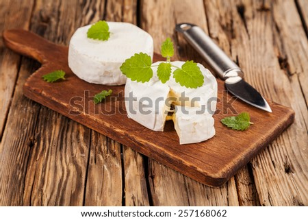 French Camembert pieces served on wood - stock photo