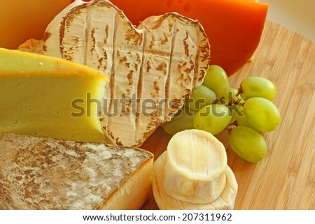 French cheese and green grapes on wooden cutting board