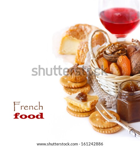 French cheese Lagres with dried fruits, confiture and crackers on a white background. - stock photo