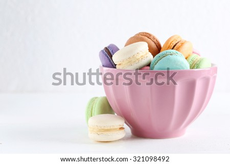 French colorful and tasty macarons in bowl on wooden table - stock photo