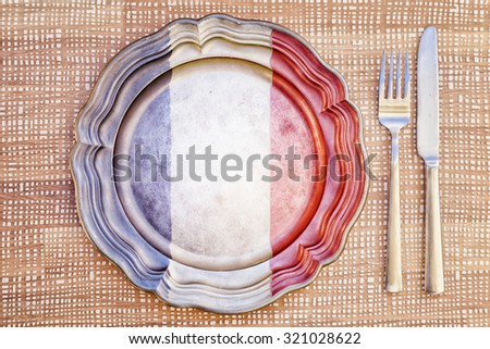 French Cuisine - Plate and Cutlery / Concept of French cuisine with empty plate colored with the colors of French flag next to silver cutlery. - stock photo
