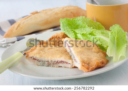 french deep fried cordon bleu with salad on white plate - stock photo