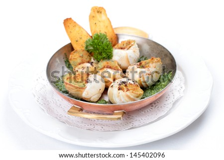 French escargot au gratin in presentation skillet with garnish and side dish