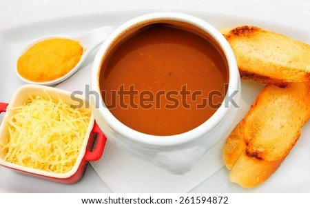 French fish soup Bouillabaisse served with pepper mayonnaise, toasted baguette and grated cheese. Selected focus on the upper part of the plate and the toasts. - stock photo