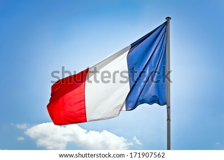 French flag in front of blue sky - French national flag on wind lighted  - stock photo