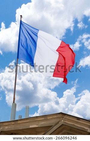 French flag on top of a building waving in the wind - stock photo