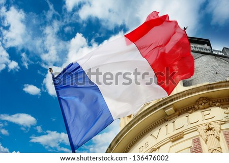 French flag waving over one Hotel de Ville - stock photo