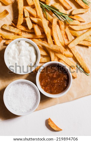 French fries and bowls with salt, ketchup and dip. - stock photo