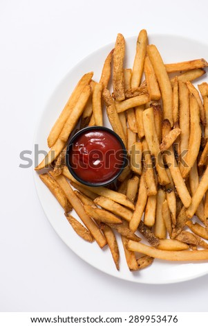 french fries and ketchup in a white plate as a snack, studio shot, close up, vertical - stock photo