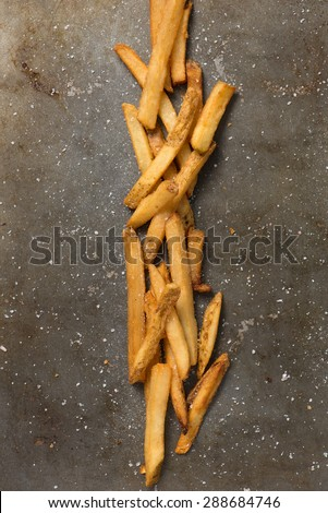 french fries and sea salt styled in a baking pan, top view, close up, vertical - stock photo
