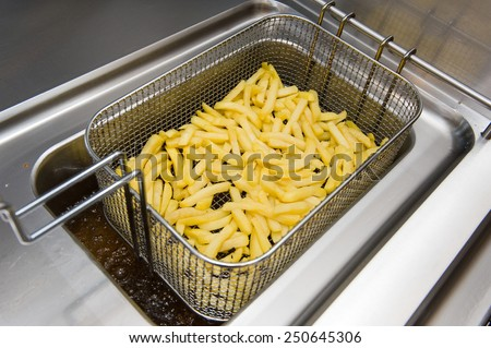French fries baking in fat in a cafetaria - stock photo