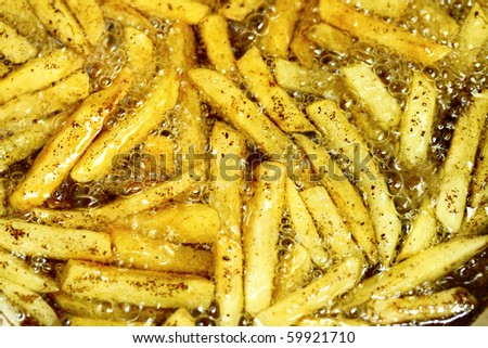 french fries - baking potatoes in hot oil - stock photo