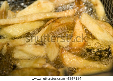 french fries cooking in hot oil - stock photo